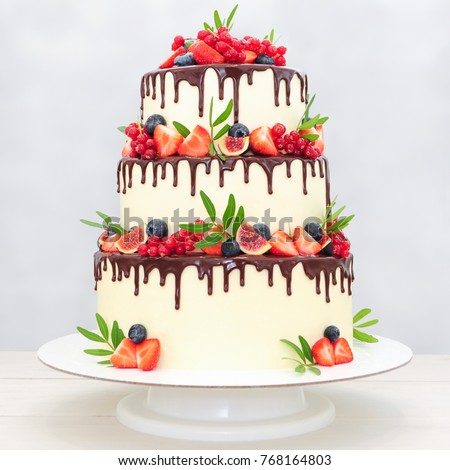 Three Tiered Wedding Cake In Chocolate, Decorated With Slices Strawberries,  Blueberries, Figs