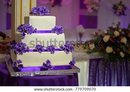 Threetiered white cake purple flowers stock photo royalty free three tiered white cake with purple flowers mightylinksfo