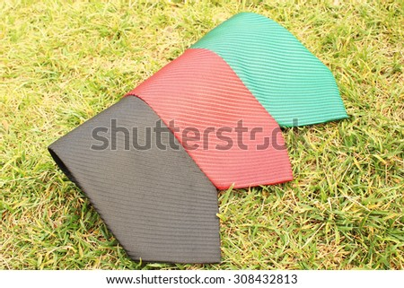 three ties white, red and black on the grass