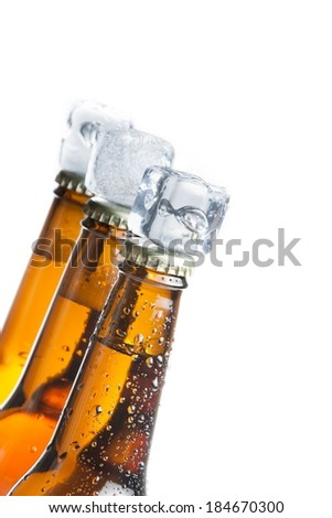 three tilted bottle of fresh beer with ice on top and drops,concept of fresh beer on summer, on white background