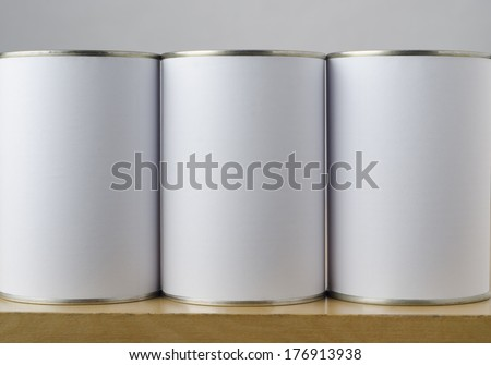 Three tin cans with blank white paper labels on a shelf, copy space on labels allows inclusion of appropriate text or images to indicate options. - stock photo