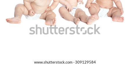 Three toddlers in diaper on a white background - stock photo
