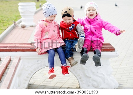 three toddlers sitting on the bench in the park