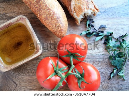 three tomatoes on the vine with oregano olive oil in a wooden bowl and Italian bread on a wooden cutting board/tomato sauce/Italian food dream - stock photo
