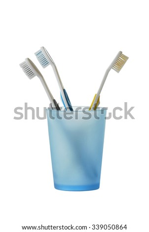 Three toothbrushes in glass isolated on white