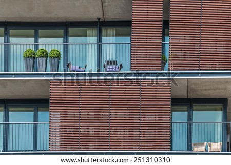 Three topiary trees on an apartment balcony in Hamburg Germany Three topiary trees in flowerpots standing in a row on an apartment balcony, closeup view of the exterior of the building - stock photo