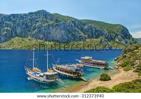three tourist boats moored at Camellia island beach with rocky island at background against clear blue sky on sunny day, Hisaronu Bay, Aegean sea, Turkey - stock photo
