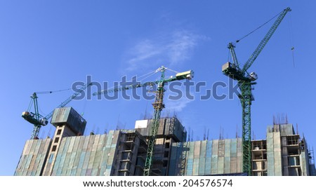three tower cranes working on top of high-rise building construction on blue sky background - stock photo