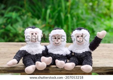 three toy cheerful monkeys sit - stock photo