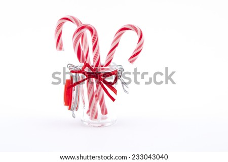 three traditional christmas candies cane in the glass on a white background - stock photo