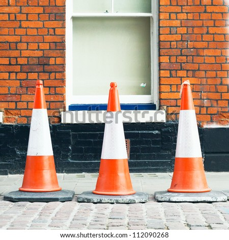 Three traffic cones in front of a brick wall - stock photo