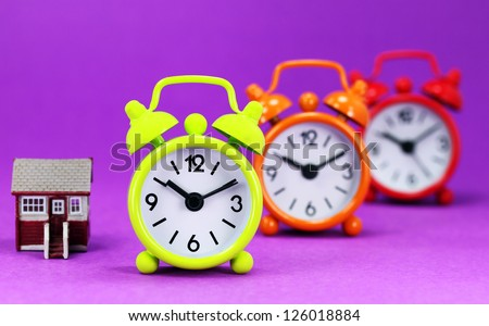 Three traffic light colored alarm clocks next to a first home buyers house, asking the question is it time to wake up to the housing market! - stock photo