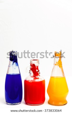Three transparent glass bottles with coloured water, blue, yellow, red, against a white background
