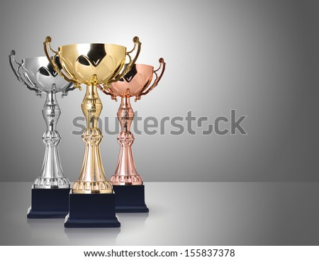 Three trophies, gold, silver and bronze on gray background - stock photo