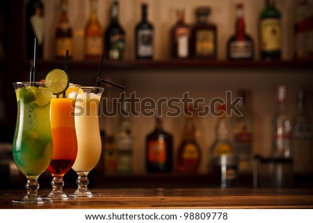 Three tropical mixed drinks, shot in bar with space for copy