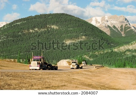 three trucks coming up the Canadian Rockies - stock photo