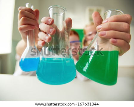 Three tubes with chemical liquids held by schoolchildren - stock photo