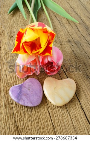 Three tulips and two stone hearts on a rustic wooden plank - stock photo
