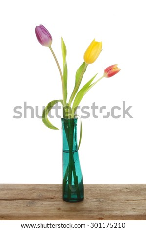 Three tulips in a vase on a wooden board against a white background - stock photo