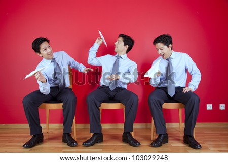 Three twin businessman sited next to a red wall trowing paper planesl