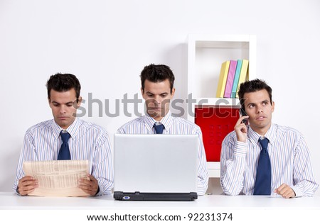 Three twin businessman working at the office, reading the newspaper, on the phone and working with the laptop