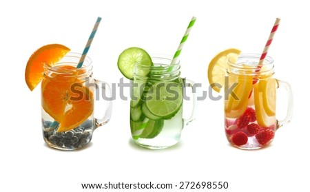 Three types of fruit filled detox water mason jars with straws isolated on a white background - stock photo
