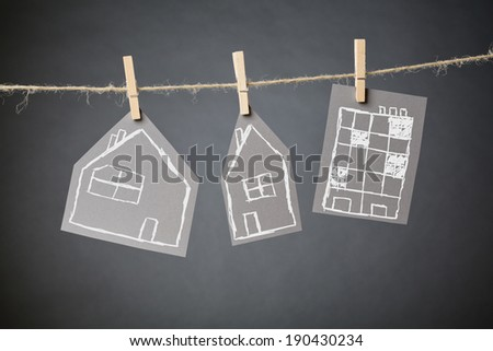 Three types of residential buildings drawn by hand on carton hanging from a rope line with clothespins. - stock photo