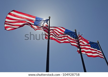 Three United States of America Flags Blowing in the Wind. - stock photo