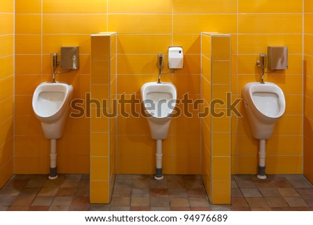 Three urinal in the bathroom with yellow walls - stock photo