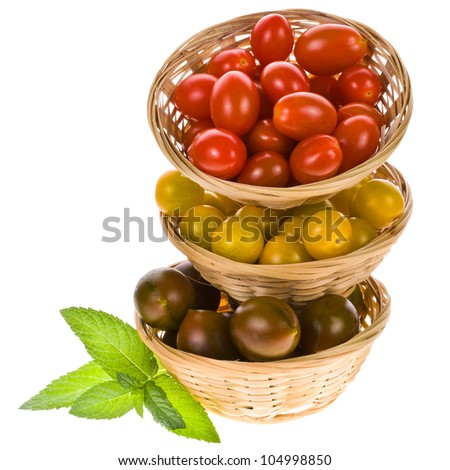 three varieties of cherry tomatoes - red, yellow and black wicker baskets in kumato. folded into the tower. isolated on a white background.
