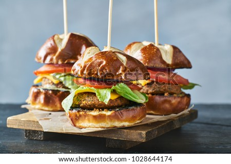 three vegan burger sliders with pretzel buns