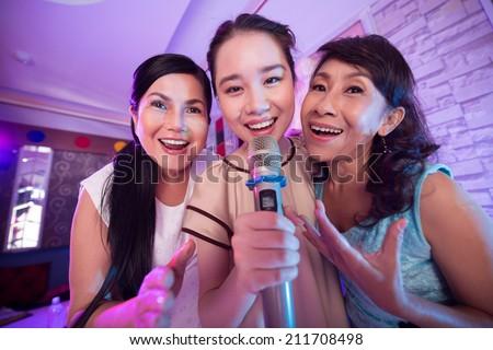 Three Vietnamese women singing a song in the karaoke bar - stock photo