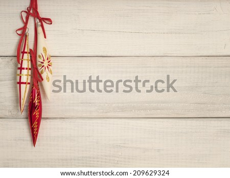 Three Vintage Christmas Ornaments Hanging on Used Rustic White Board Background with room or space for copy, text, words.  Horizontal, warm still life for a card or invite - stock photo