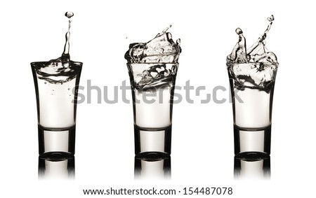 Three vodka glasses with splashes, clipping path is included - stock photo