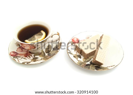 three wafers and cup of tea with lemon on white