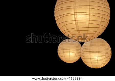Three warmly colored balloon paper lamps isolated on black background