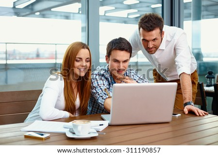 Three web designers looking at laptop