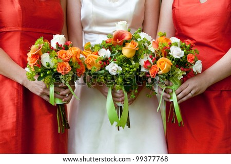 three wedding bouquets being held by a bride and her bridesmaids - stock photo