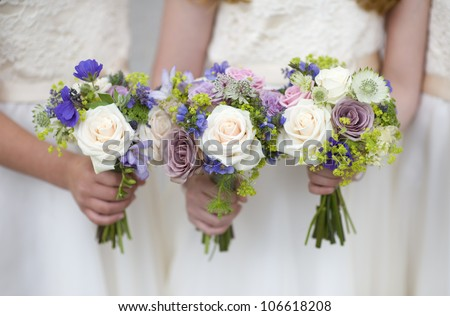 three wedding bouquets held by bridesmaids or flowergirls - stock photo