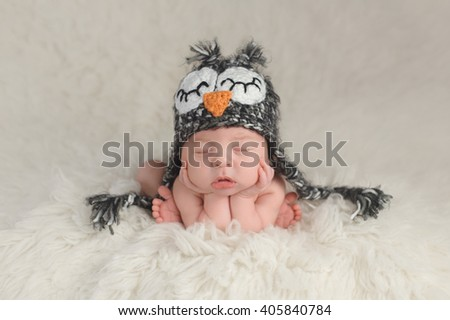 Three week old newborn baby boy wearing a crocheted owl hat. He's in a cute, curled up, chin on hands pose and sleeping on a white flokati rug. - stock photo