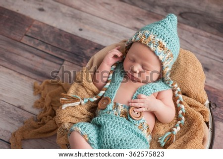 Three week old newborn baby boy wearing an aqua blue, crocheted pixie hat, shorts and suspenders. He is sleeping in a bucket. Shot in the studio on a wood background.