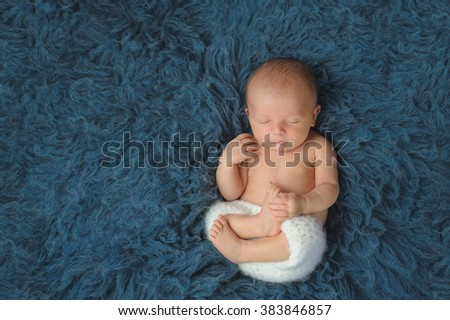 Three week old newborn baby boy wearing white, crocheted shorts. He is sleeping on his back on a dark blue flokati rug. Shot from a high angle view.