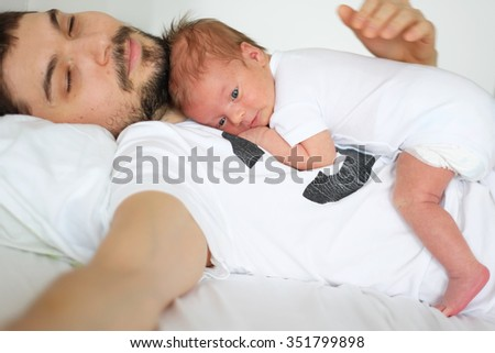 Three weeks old newborn with his father. Shallow depth of field.  - stock photo