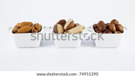 Three white ceramic bowls, with almond, Brazil nut and hazelnut. - stock photo