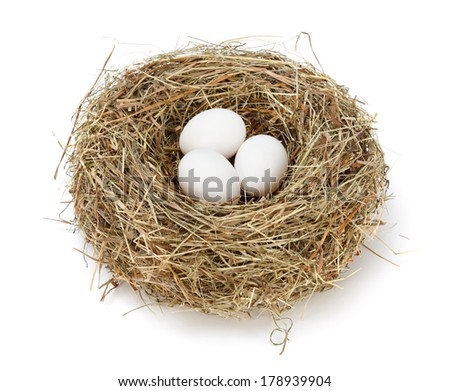 Three white chicken eggs in hay nest