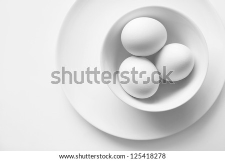 Three white chicken eggs on a plate