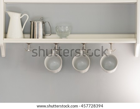 three white coffee cups hanging in a row. jug and glass and stainless cordless kettle sitting on shelf - stock photo