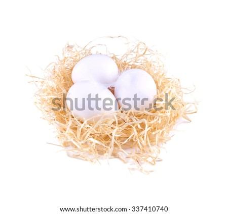 Three white eggs in the straw. White eggs in the nest isolated.