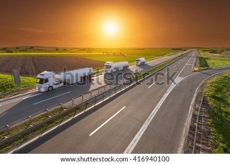 Three white gasoline tanker trucks in line driving towards the sun. Fast gasoline delivery on the freeway at beautiful sunset. Freight scene on the motorway near Belgrade, Serbia. - stock photo