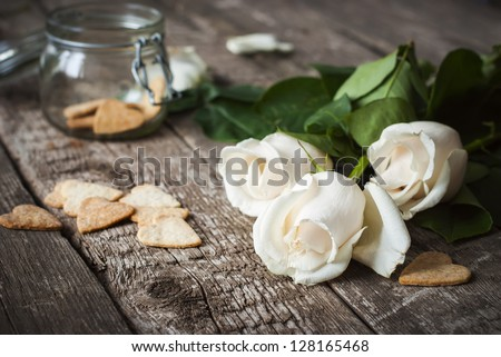 Three White Roses and Pastry on the Wooden Table Background - stock photo